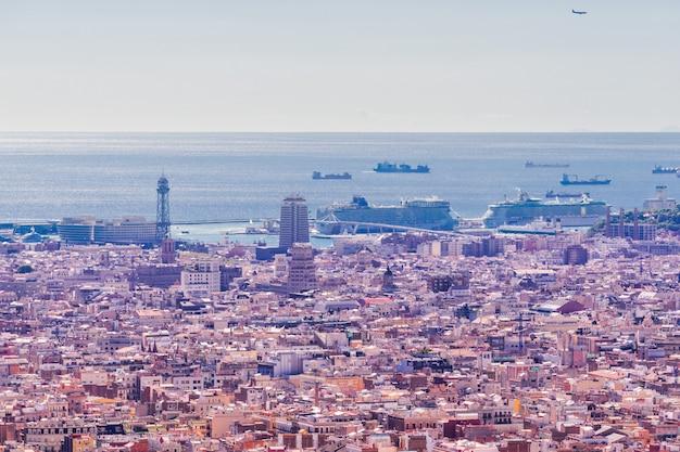 Vue panoramique de la ville de barcelone depuis la plus haute colline. le soleil du jour éclaire toute la ville