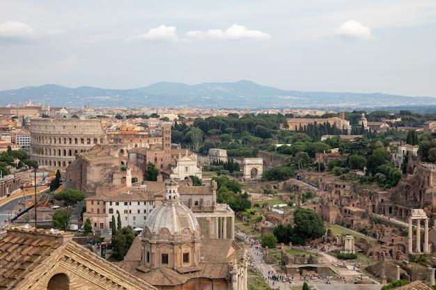 Vue panoramique de la ville de rome avec forum romain et colisée du monument vittorio emanuele ii également connu sous le nom de vittoriano. journée ensoleillée d'été et ciel bleu dramatique