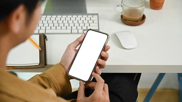 Vue par-dessus l'épaule d'un homme d'affaires utilisant un téléphone intelligent au bureau.