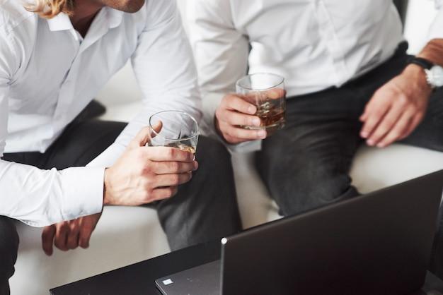 Vue particulaire des deux hommes d'affaires assis près de l'ordinateur portable et tenant un verre de whisky.