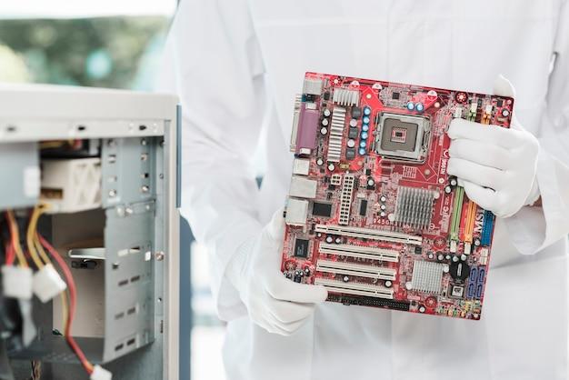 Vue de la partie médiane de la main de technicien tenant la carte de circuit informatique