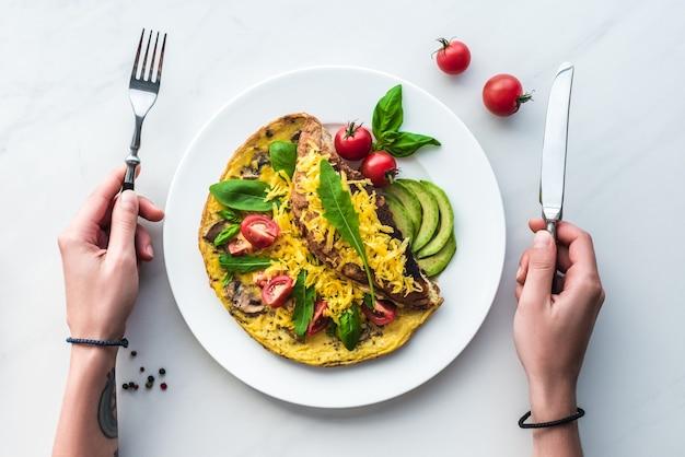 Vue partielle d'une femme avec des couverts en mains sur une table avec une omelette maison pour le petit-déjeuner