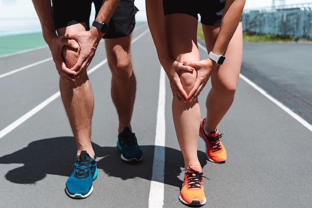 Vue partielle des joggeurs dans les smartwatches se réchauffant sur la piste de course