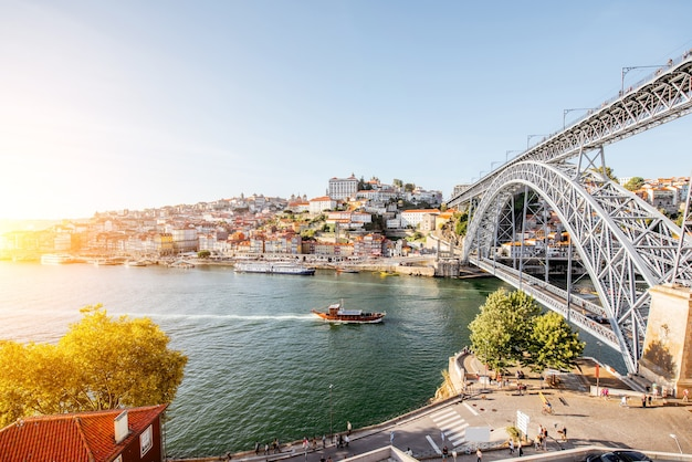Vue paysage la belle vieille ville avec le célèbre pont de fer au-dessus du fleuve douro pendant le coucher du soleil dans la ville de porto, portugal