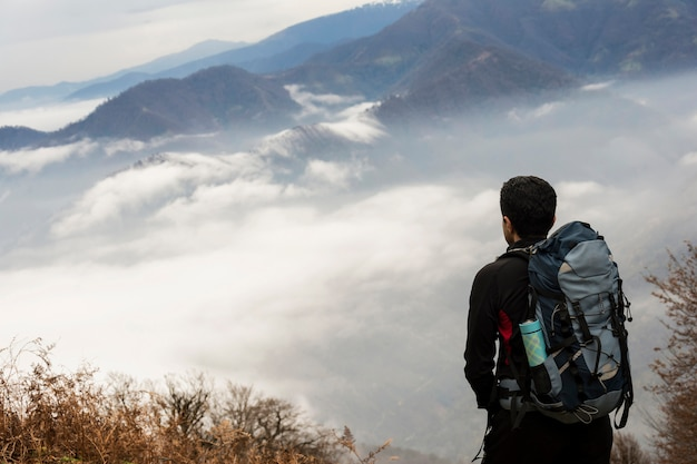 Vue de paysage de collines de montagne automne brumeux et randonneur avec sac à dos au premier plan