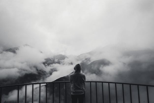Vue paysage de collines de montagne d'automne brumeux recouvert de brouillard et silhouette homme dans une hotte. photo monochrome