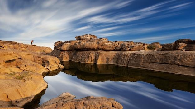 Vue paysage d'un lac dans un grand canyon en thaïlande avec petit photographe loin sur un rocher