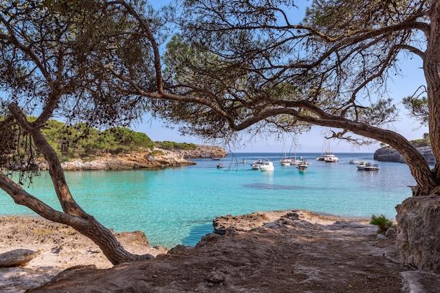 Vue sur le paysage marin de la célèbre baie de cala turqueta avec des bateaux sur la mer. minorque, iles baléares, espagne