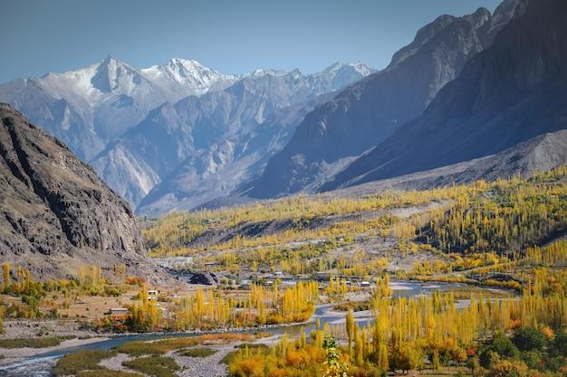 Vue de paysage de la rivière qui traverse la forêt à gupis avec la chaîne de montagnes en arrière-plan.