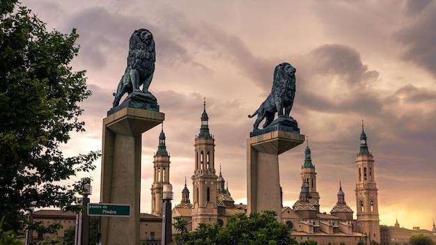 Vue sur le paysage urbain de la sculpture de lions de bronze sur le pont avec les toits et les flèches de la basilique de notre-dame à l'arrière-plan de la ville de saragosse. monument historique cathédrale d'aragon. église catholique espagne