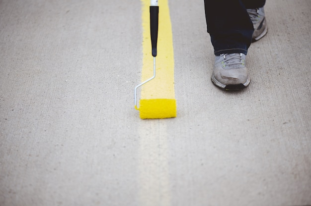 Vue d'une personne repeignant les lignes de stationnement de l'asphalte d'un parking avec de la peinture jaune