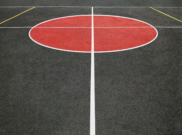 Vue en perspective du cercle central du terrain de sport avec des lignes blanches. terrain de jeu noir et rouge
