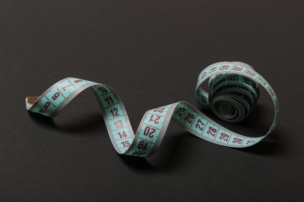 Vue en perspective du ruban à mesurer enroulé sur fond noir. concept de maintien en forme.