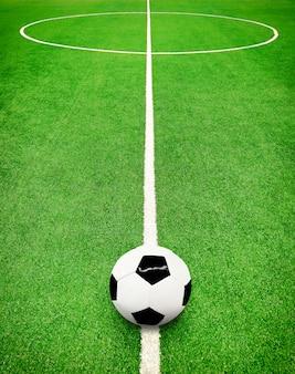 Vue en perspective du terrain de football vert avec des lignes blanches et ballon de football
