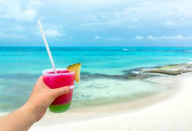 Vue en perspective personnelle d'une femme tenant un verre et buvant un cocktail à la mer des caraïbes