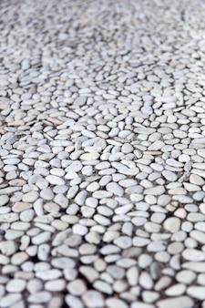 Vue en perspective de petites pierres rondes dans le mur de béton