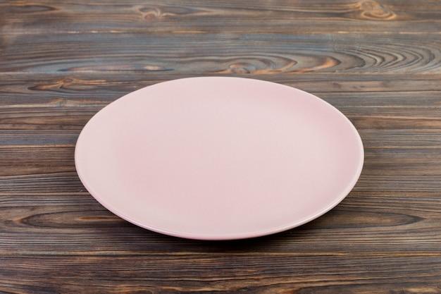 Vue de perspective. plat de matte rose vide pour le dîner sur un fond en bois foncé