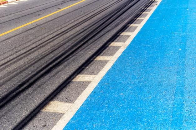 Vue en perspective de la route goudronnée, peinture de couleur bleue pour piste cyclable.