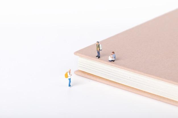 Vue de petites figurines d'étudiants debout autour d'un manuel sur blanc