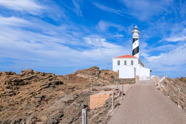 Vue sur le phare (faro de favaritx) par temps ensoleillé avec de beaux nuages dans le ciel sur l'île de minorque, îles baléares, espagne