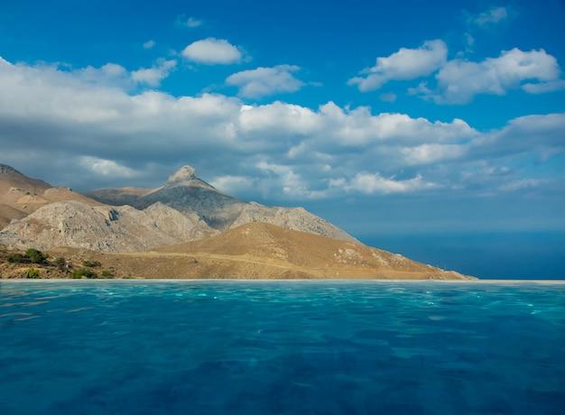 Vue de la piscine à la montagne et au ciel bleu