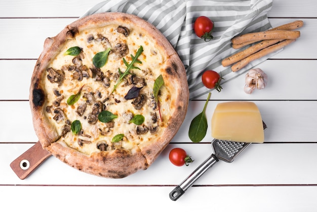 Vue sur la pizza aux champignons maison et bâtons de pain avec des ingrédients sur une planche blanche