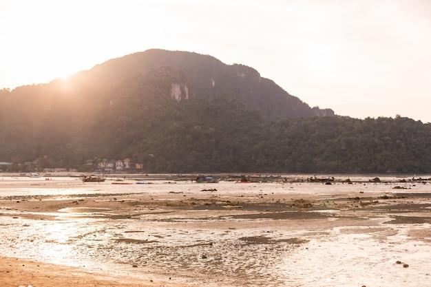 Vue de la plage sur une île tropicale verte à marée basse au coucher du soleil.