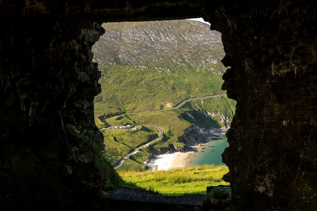 Vue sur la plage de keem à partir d'une fenêtre d'un vieux bâtiment achill island county mayo irlande