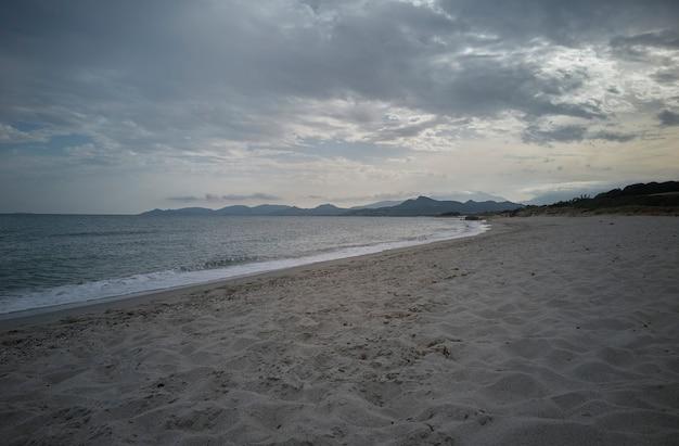 Vue sur la plage de piscina rei dans le sud de la sardaigne complètement libre de touristes pendant le coucher du soleil.