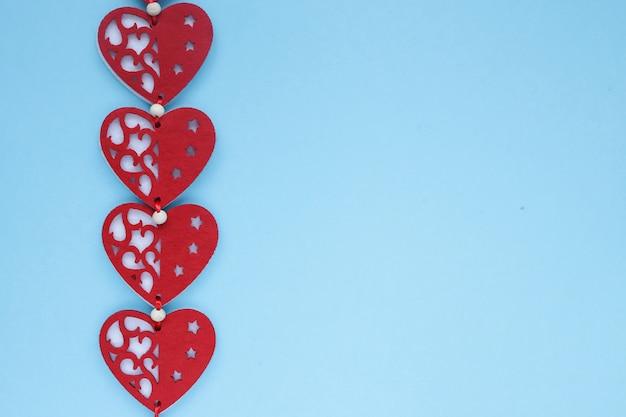 Vue à plat des coeurs de la saint-valentin sur fond bleu. symbole d'amour et concept de la saint-valentin. copyplace, espace pour le texte et le logo.