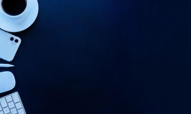 Vue plate fond bleu avec une tasse de café souris et clavier stylo mobile