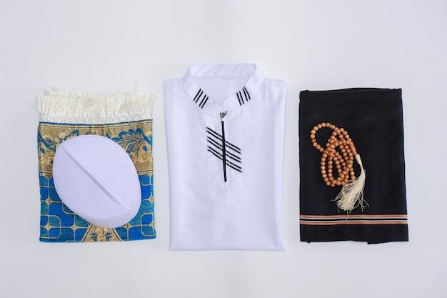 Vue plate et vue de dessus de la robe traditionnelle musulmane et des accessoires pour prier avec des perles de prière