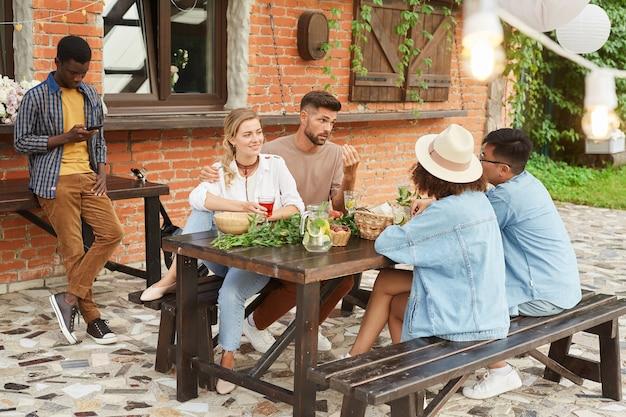 Vue pleine longueur au groupe multiethnique de jeunes appréciant le dîner en plein air