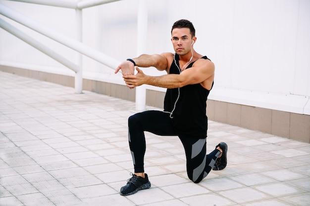 Vue de pleine longueur de gars sportif faisant des exercices physiques pour les bras et les jambes, s'étendant à l'extérieur
