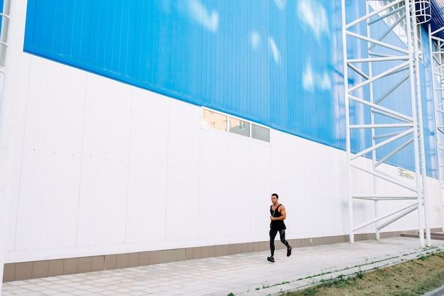 Vue de pleine longueur de jeune sportif en vêtements de sport noir lors de la course à l'extérieur.