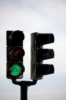 Vue d'un pôle de feu de signalisation à double fourche avec un feu vert.