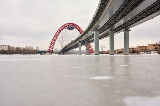 Vue sur le pont routier avec une arche rouge, le pont pittoresque sur la rivière de moscou, le pont pittoresque avec une soucoupe volante