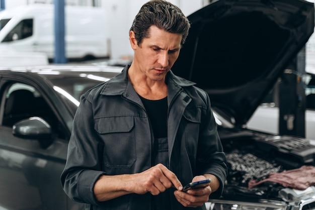 Vue portrait du mécanicien automobile debout avec son smartphone et vérifiant quelque chose. concept de service automobile et de réparation automobile