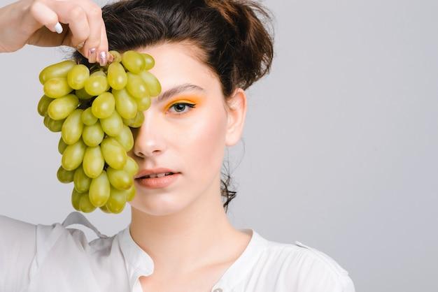 Vue portrait de la femme brune caucasienne cache son œil derrière le raisin vert et regarde la caméra avec plaisir. stock photo