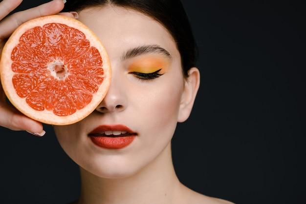 Vue portrait de la jolie femme caucasienne tendre avec un maquillage lumineux tenant un pamplemousse et cachant un œil derrière elle. isolé sur fond noir