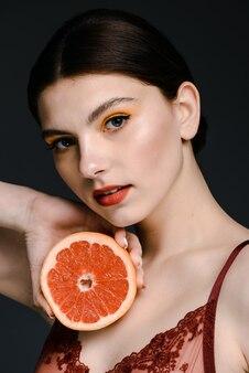 Vue portrait de la jolie femme caucasienne tendre avec un maquillage lumineux tenant un pamplemousse près de son cou et posant pour la caméra isolée sur fond noir