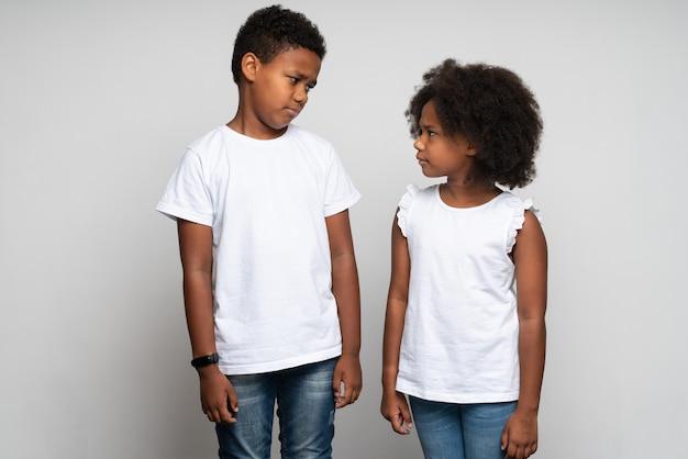 Vue portrait à la taille du garçon triste regardant avec des émotions malheureuses sa sœur tout en posant au studio avec un mur blanc. notion de relations familiales