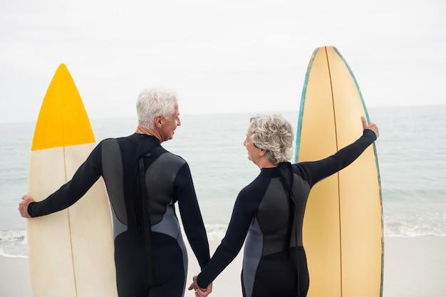 Vue postérieure, de, couples aînés, à, planche surf, tenant main, sur, plage