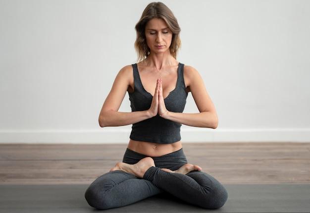 Vue postérieure, de, femme, faire, yoga, sur, tapis
