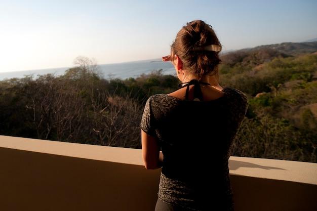 Vue postérieure, de, femme, regarder dessus, sommet colline, à, horizon, depuis, a, balcon