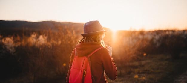 Vue postérieure, de, fille, randonnée, seul, pendant, coucher soleil