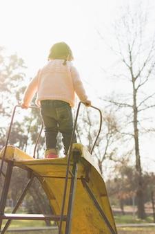 Vue postérieure, de, girl, debout, sur, diapositive, dans parc