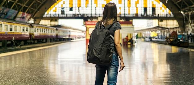 Vue postérieure, de, jeune, femme asiatique, voyageur, à, petit sac à dos, sur, les, chemin fer, stantion., attente, pour, train, pour, transport, sur, vacances, voyage., voyage, concept