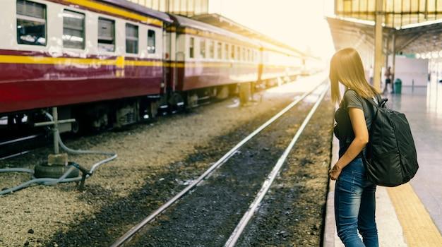 Vue postérieure, de, jeune, femme asiatique, voyageur, à, petit sac à dos, sur, les, chemin fer, stantion., attente, pour, train, à, transport, sur, vacances, trip.