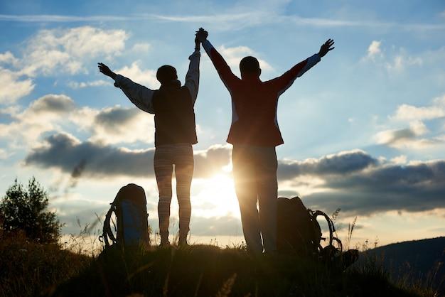 Vue postérieure, type, et, girl, tenant mains haute, a élevé leurs mains, contre, a, coucher soleil, dans montagnes